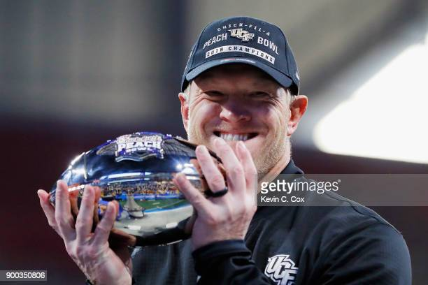 Head coach Scott Frost of the UCF Knights holds the trophy after defeating the Auburn Tigers 3427 to win the ChickfilA Peach Bowl at MercedesBenz...