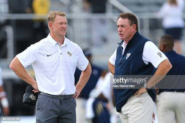 Head coach Scott Frost of the UCF Knights speaks with head coach Butch Davis of the FIU Panthers during a NCAA football game between the Florida...