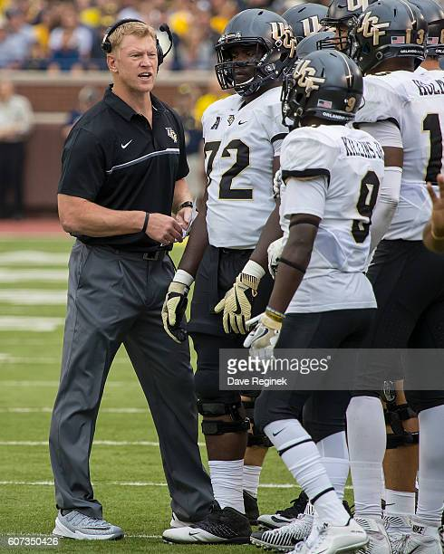 Head coach Scott Frost of the UCF Knights talks to his team on a play stoppage in the first quarter during a college football game against the...