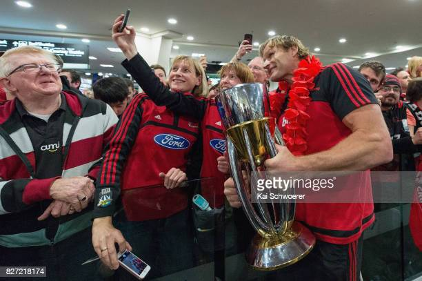 Head Coach Scott Robertson of the Crusaders presents the Super Rugby trophy to fans during the Crusaders arrival at Christchurch Airport on August 7...