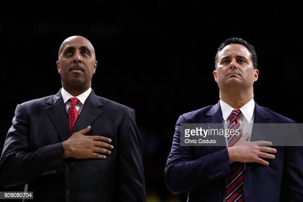 Head coach Sean Miller and associate head coach Lorenzo Romar of the Arizona Wildcats stand for the National Anthem before the college basketball...