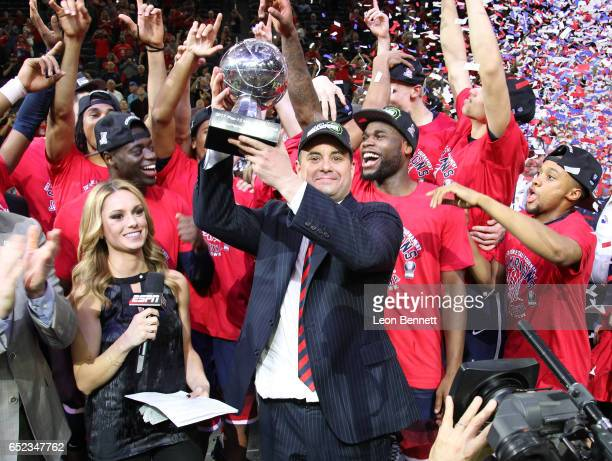 Head coach Sean Miller holds up the trophy after defeating the Oregon Ducks 8380 to win the championship game of the Pac12 Basketball Tournament at...