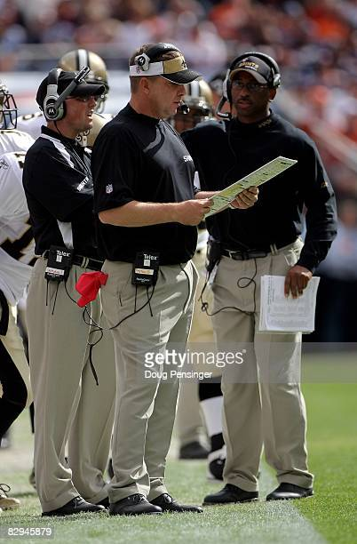 Head coach Sean Payton of the New Orleans Saints is flanked by quarterback coach Pete Carmichael Jr and wide receiver coach Curtis Johnson as they...