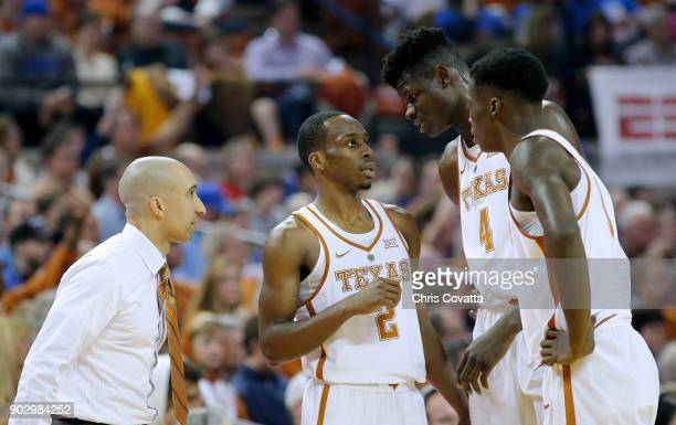Head coach Shaka Smart listens as Matt Coleman gives instructions to Mohamed Bamba and Andrew Jones of the Texas Longhorns during the game with the...