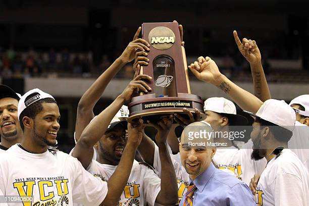 Head coach Shaka Smart of the Virginia Commonwealth Rams holds up the trophy after defeating the Kansas Jayhawks during the southwest regional final...