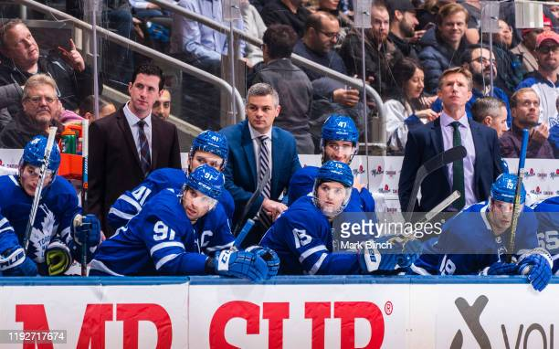Head coach Sheldon Keefe, assistant coach Paul McFarland, and assistant coach Dave Hakstol of the Toronto Maple Leafs watch from the bench against...