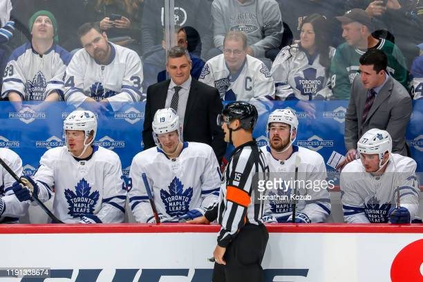 Head Coach Sheldon Keefe of the Toronto Maple Leafs chats with referee Jean Hebert during a first period stoppage in play against the Winnipeg Jets...