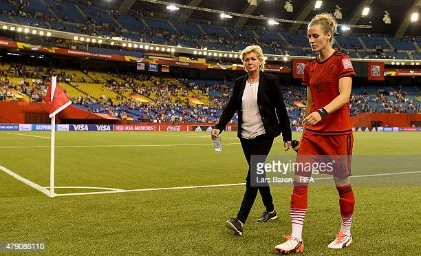 Head coach Silvia Neid and Simone Laudehr of Germany leave dejected the pitch after loosing the FIFA Women's World Cup 2015 Semi Final match between...