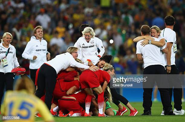 Head coach Silvia Neid of Germany celebrates with their players following the Women's Olympic Gold Medal match between Sweden and Germany at Maracana...