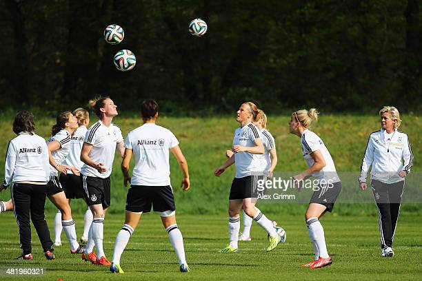 Head coach Silvia Neid of Germany walks past players exercising during a Germany Women's training session at the Commerzbank Arena training ground on...