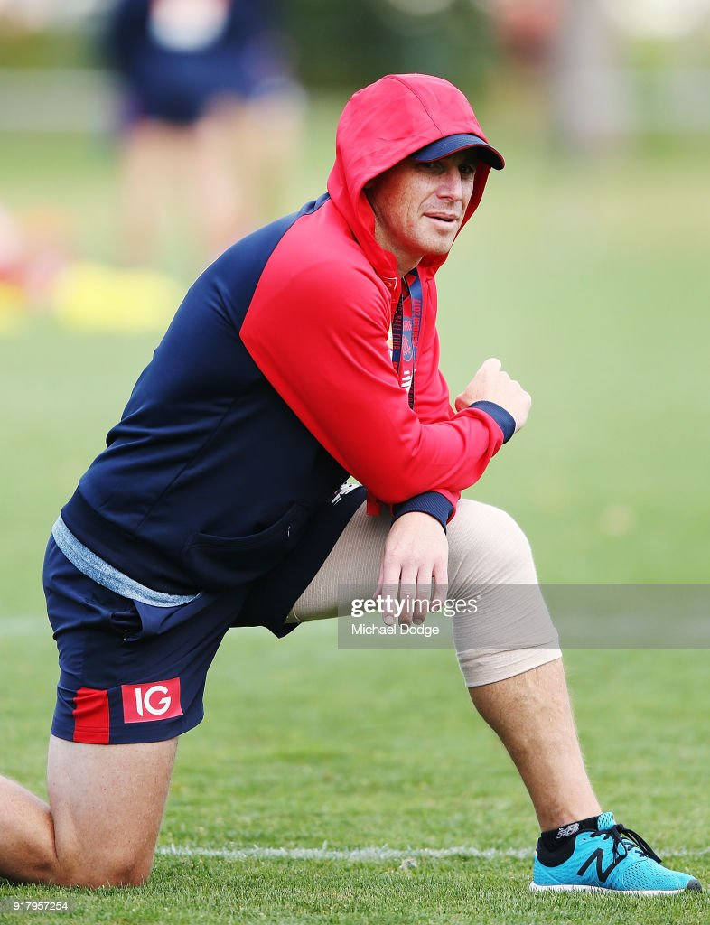 Head coach Simon Goodwin looks upfield with a bandaged left knee during a Melbourne Demons AFL training session at Gosch's Paddock on February 14, 2018 in Melbourne, Australia.