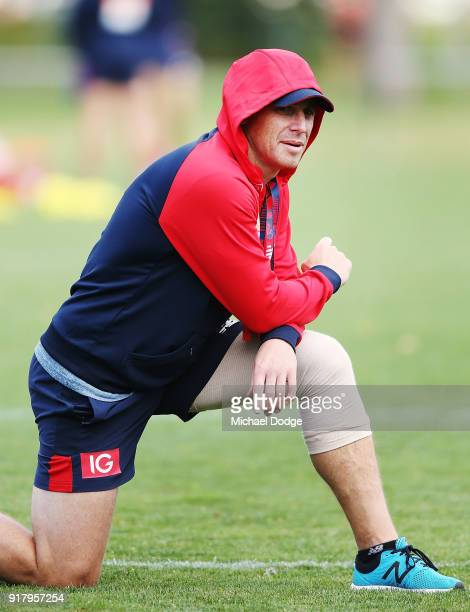 Head coach Simon Goodwin looks upfield with a bandaged left knee during a Melbourne Demons AFL training session at Gosch's Paddock on February 14...
