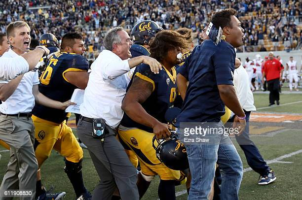 Head coach Sonny Dykes and James Looney of the California Golden Bears celebrate with teammates after they beat the Utah Utes at California Memorial...
