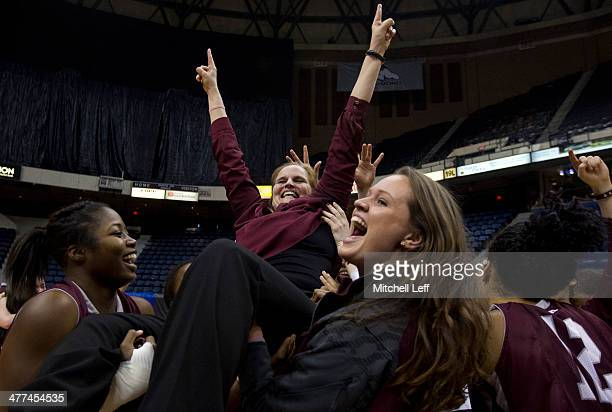 Head coach Stephanie Gaitley of the Fordham Rams is lifted in the air by her team in celebration of their win over the Dayton Flyers in the...