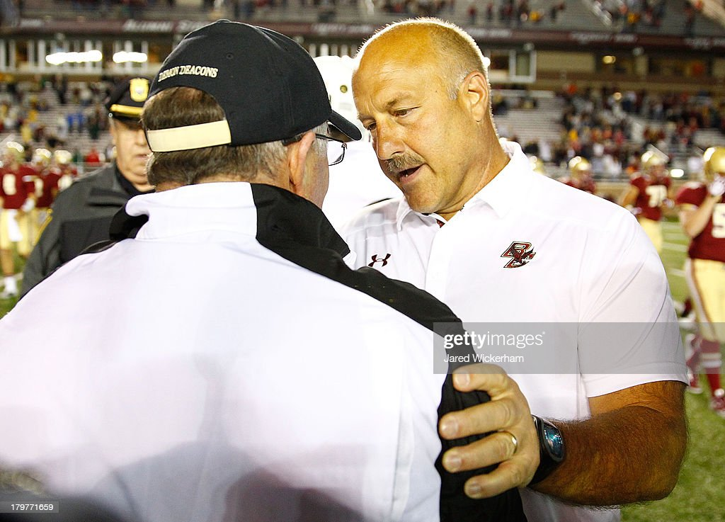 Head coach Steve Addazio of the Boston College Eagles shakes hands with head coach Jim Grobe of the Wake Forest Demon Deacons following their game on September 6, 2013 at Alumni Stadium in Chestnut Hill, Massachusetts.