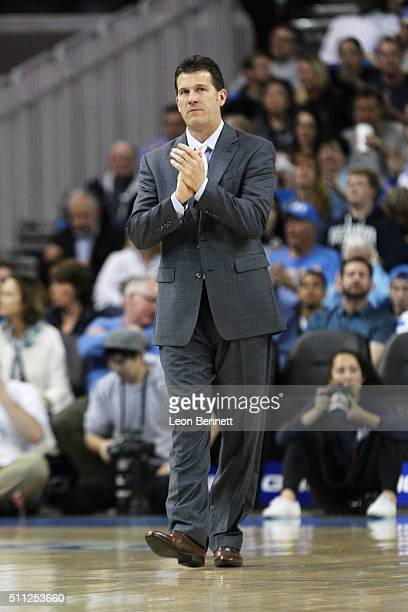 Head coach Steve Alford of the UCLA Bruins cheers on his team during a timeout against the Utah Utes during a NCAA PAC12 college basketball game at...