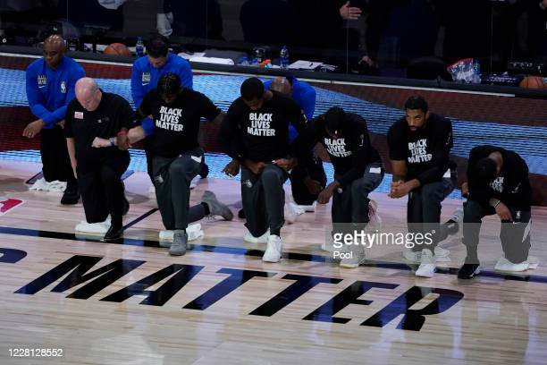 Head coach Steve Clifford and players of the Orlando Magic lock arms as they kneel for the national anthem before an NBA basketball first round...
