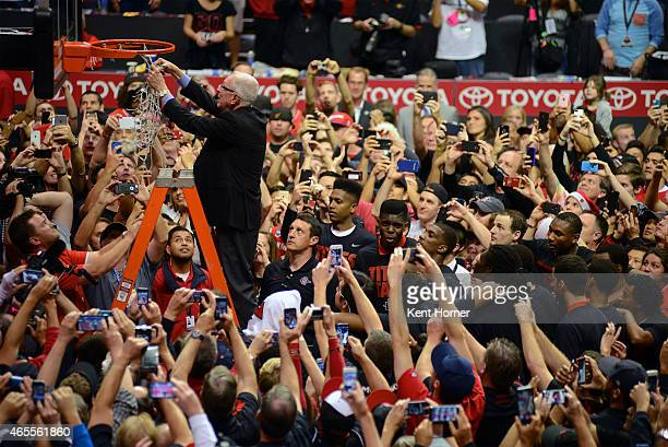 Head coach Steve Fisher of the San Diego State Aztecs helps cut down the net in celebration of their cochampion title of the Mountain West Conference...