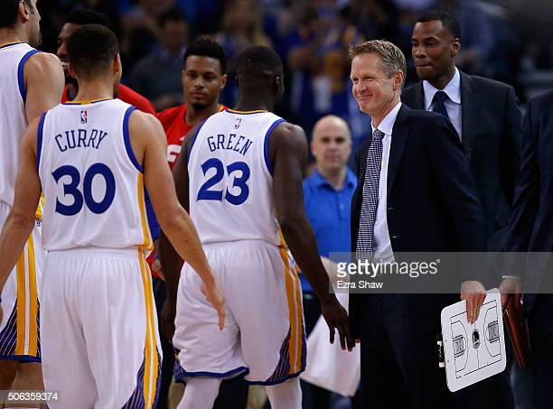 Head coach Steve Kerr of the Golden State Warriors congratulates Draymond Green and Stephen Curry during a time out of their game against the Indiana...