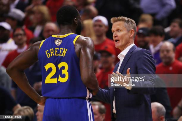 Head coach Steve Kerr of the Golden State Warriors speaks to Draymond Green during a timeout against the Toronto Raptors in the first half during...