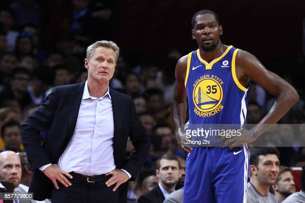 Head coach Steve Kerr of the Golden State Warriors speaks to Kevin Durant during the game between the Minnesota Timberwolves and the Golden State...