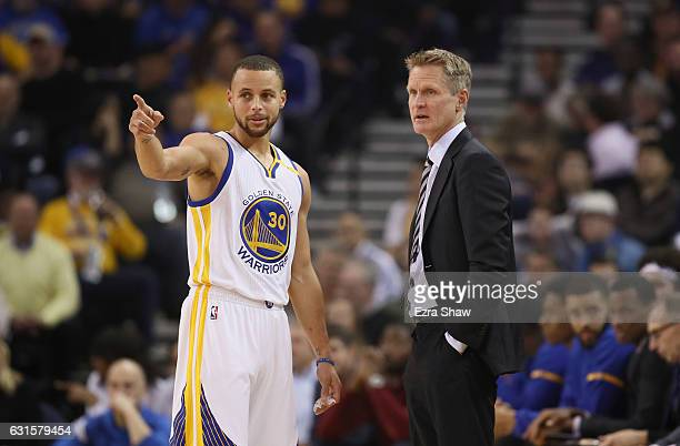 Head coach Steve Kerr of the Golden State Warriors talks to Stephen Curry of the Golden State Warriors during their game against the Detroit Pistons...