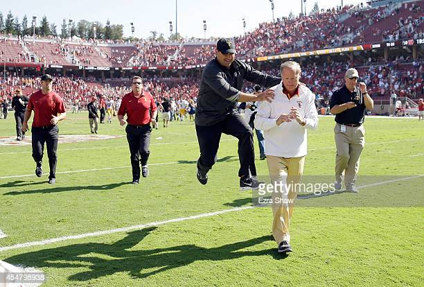 USC head coach Steve Sarkisian jumps in celebration with Athletic Director Pat Haden after they beat the Stanford Cardinal at Stanford Stadium on...