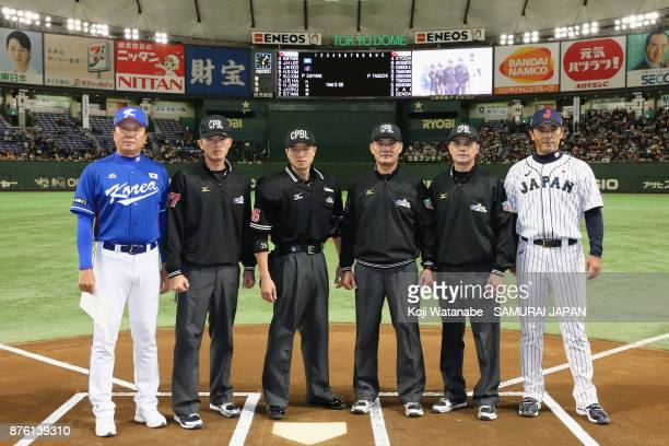 Head coach Sun Dongyol of South Korea and Head coach Atsunori Inaba of Japan pose for photographs with umpires prior to the Eneos Asia Professional...