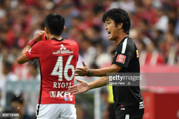 Head coach Takafumi Hori of Urawa Red Diamonds gives instruction to Ryota Moriwaki during the JLeague J1 match between Urawa Red Diamonds and Omiya...
