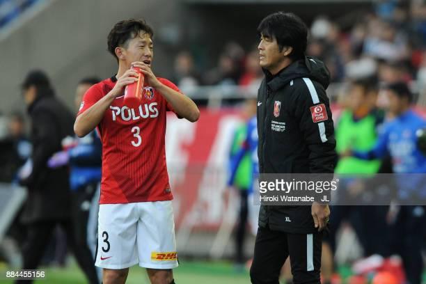 Head coach Takafumi Hori of Urawa Red Diamonds gives instruction to Tomoya Ugajin during the JLeague J1 match between Urawa Red Diamonds and Yokohama...