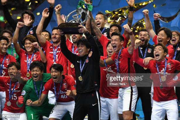Head coach Takafumi Hori of Urawa Red Diamonds lifts the AFC Champions League trophy at the award ceremony during the AFC Champions League Final...