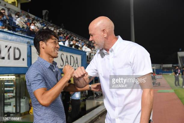 Head coach Takahiro Shimotairaof Yokohama FC and head coach Antonio Carlos of Kashima Antlers elbow bump prior to the J.League Meiji Yasuda J1 match...