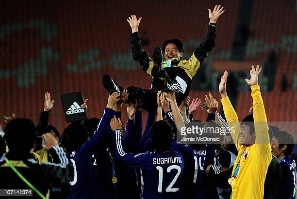 Head Coach Takashi Sekizuka of Japan is thrown in the air by the team after they won gold in the Men's Final between United Arab Emirates and Japan...