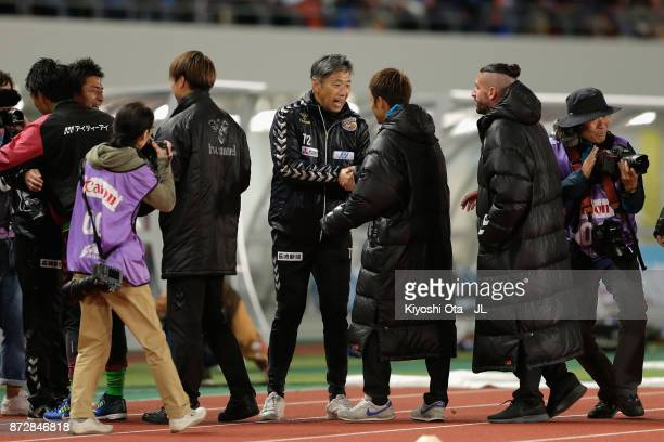 Head coach Takuya Takagi of VVaren Nagasaki celebrates with his team staffs after his team's promotion to the J1 after their 31 victory in the...