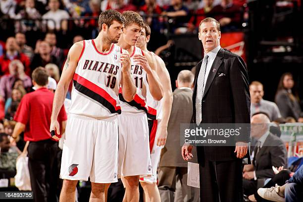 Head Coach Terry Stotts of the Portland Trail Blazers speaks with Joel Freeland and Meyers Leonard during a game against the Brooklyn Nets on March...