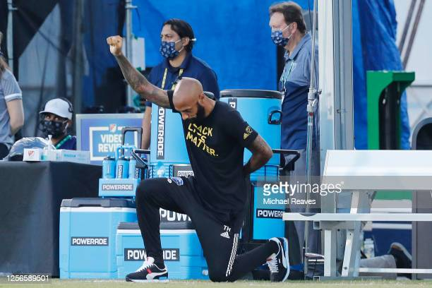 Head coach Thierry Henry of Montreal Impact takes a knee in support of the Black Lives Matter movement prior to a Group C match against Toronto FC as...