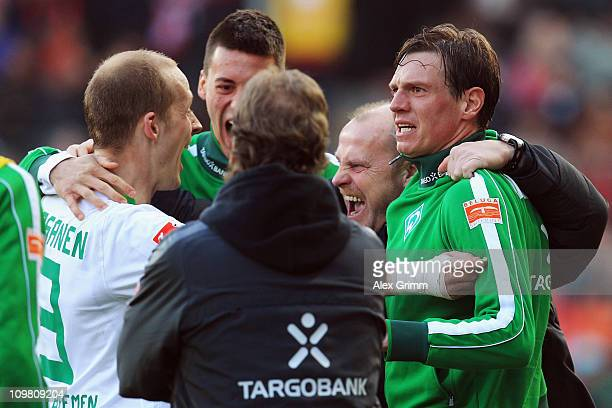 Head coach Thomas Schaaf of Bremen celebrates with Petri Pasanen Sandro Wagner and Tim Borowski after Marko Marin scored his team's third goal during...