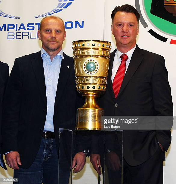 Head coach Thomas Schaaf of Werder Bremen and head coach Louis van Gaal of Bayern Muenchen pose with the trophy during a press conference prior to...