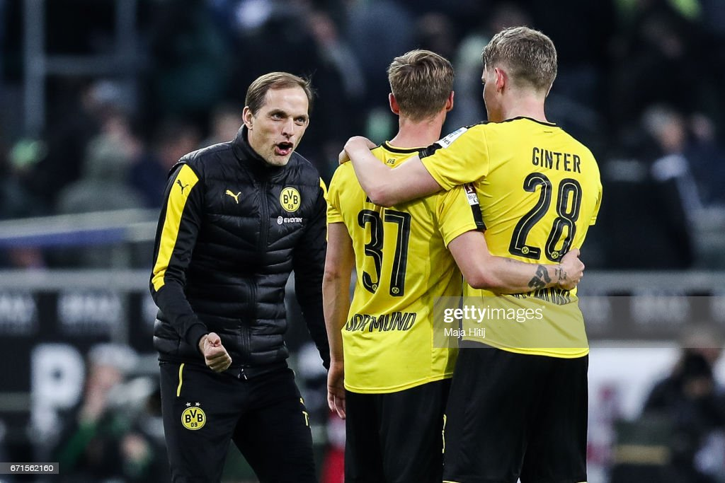 Head coach Thomas Tuchel of Dortmund (L-R), Erik Durm and Matthias Ginter celebrate after the Bundesliga match between Borussia Moenchengladbach and Borussia Dortmund at Borussia-Park on April 22, 2017 in Moenchengladbach, Germany.
