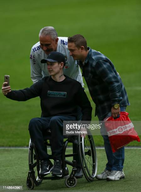 Head coach Tite attends a wheelchair fan during a training session at Beira Rio stadium on June 08, 2019 in Porto Alegre, Brazil.