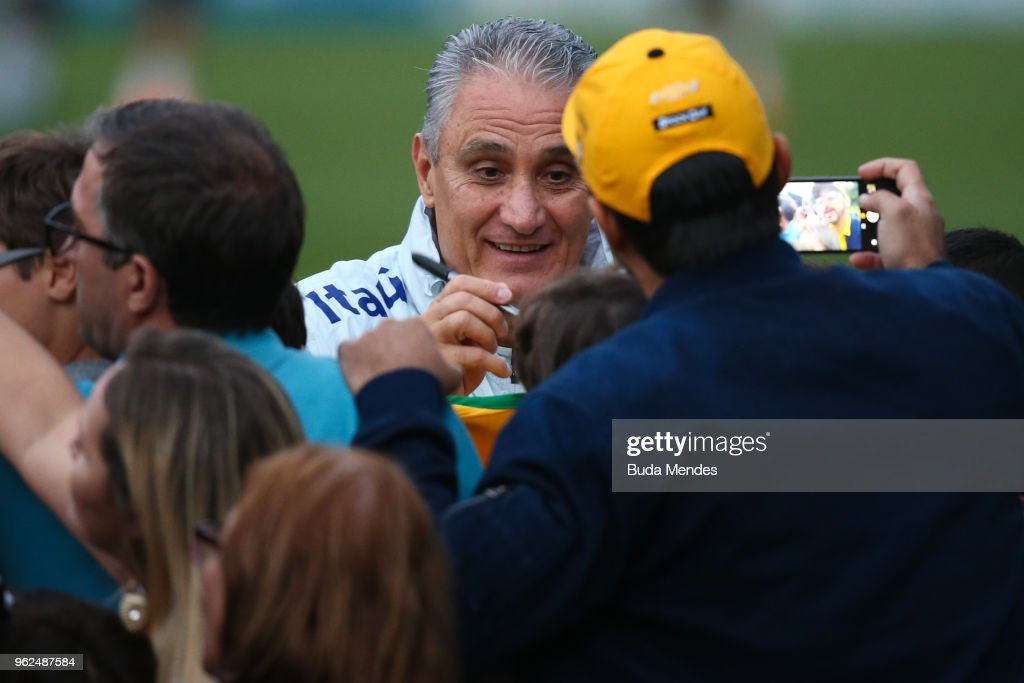 Head coach Tite signs autographs to supporters after a training session of the Brazilian national football team at the squad's Granja Comary training complex on May 25, 2018 in Teresopolis, Brazil.
