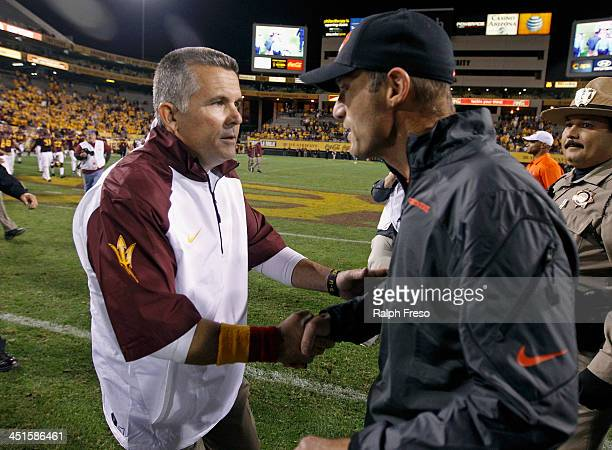 Head coach Todd Graham of the Arizona State Sun Devils and head coach Mike Riley of the Oregon State Beavers exchange handshakes at midfield after...
