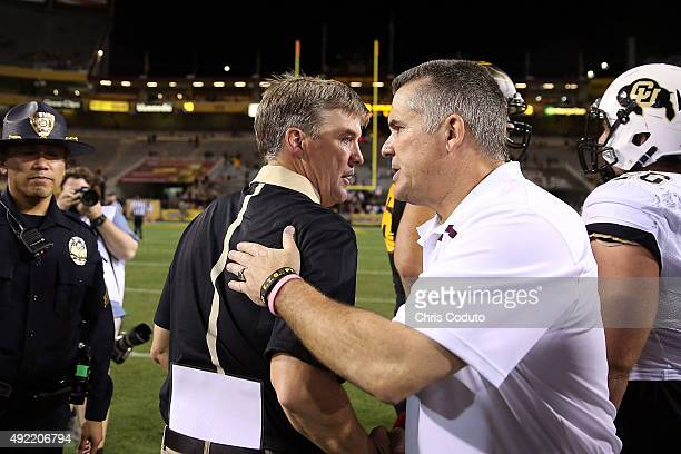 Head coach Todd Graham of the Arizona State Sun Devils shakes hands with head coach Mike MacIntyre of the Colorado Buffaloes after the college...