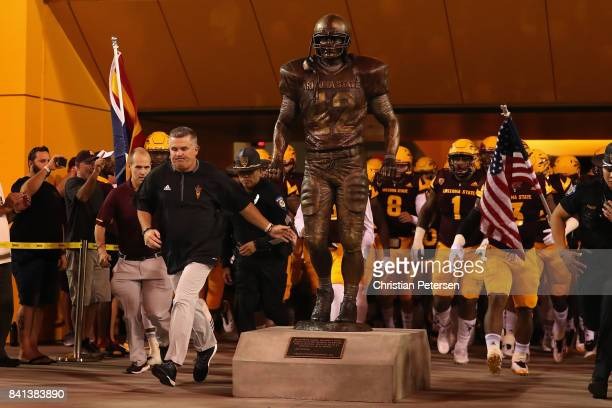 Head coach Todd Graham of the Arizona State Sun Devils touches the new Pat Tillman statue as he leads his team onto the field before the college...