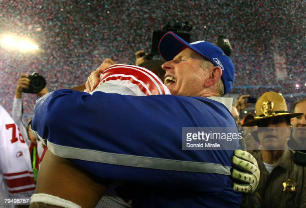 Head coach Tom Coughlin of the New York Giants hugs Osi Umenyiora after the Giants defeated the New England Patriots 17-14 during Super Bowl XLII on...