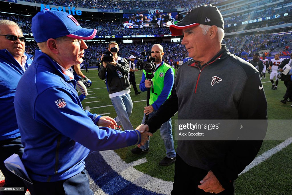 Head coach Tom Coughlin of the New York Giants talks with head coach Mike Smith of the Atlanta Falcons after their game at MetLife Stadium on October 5, 2014 in East Rutherford, New Jersey. The New York Giants defeated the Atlanta Falcons 30 - 20.