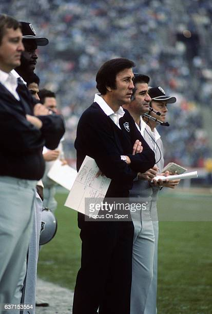 Head coach Tom Flores of the Los Angeles Raiders talks with his quarterback Jim Plunkett on the sidelines during an NFL football game circa 1984 at...