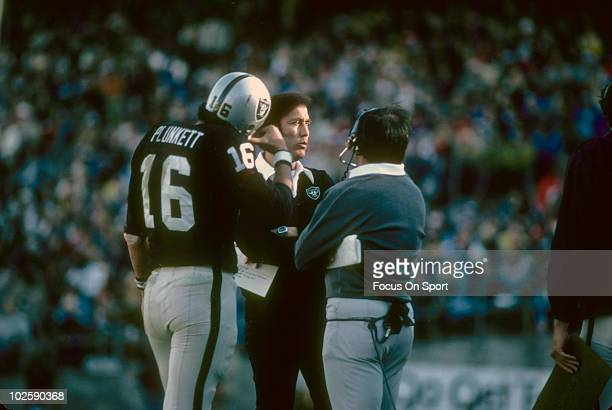 Head Coach Tom Flores of the Oakland Raiders talks with quarterback Jim Plunkett and one of his coaches circa 1981 during an NFL football game at the...
