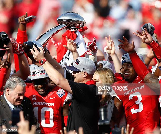 Head coach Tom Herman of the Houston Cougars raises the AAC Championship Trophy after defeating the Temple Owls at TDECU Stadium on December 5, 2015...