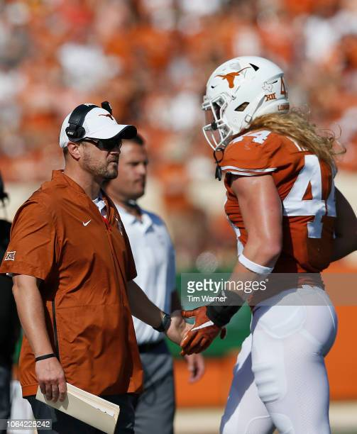 Head coach Tom Herman of the Texas Longhorns greets Breckyn Hager on the sideline in the first quarter against the West Virginia Mountaineers at...